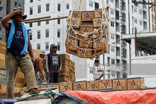 Workers load boxes of wheat flour on to a ship for transport to Sumatra Island at Sunda Kelapa port