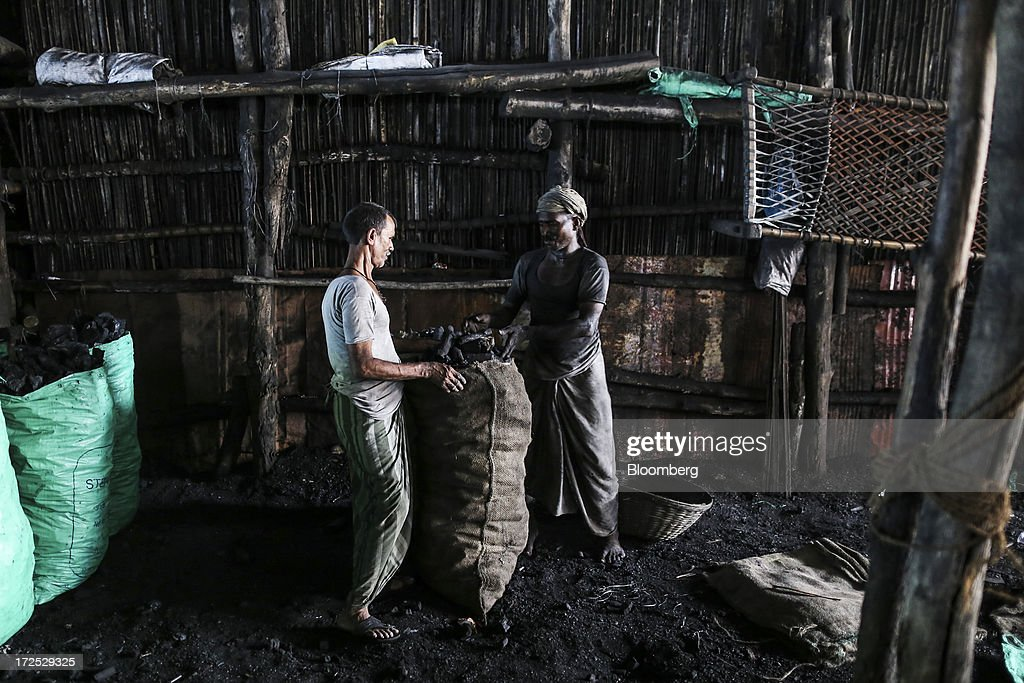 Workers load coal into a sack at a coal wholesale market in Mumbai, India, on Tuesday, July 2, 2013. India, the worlds third-largest coal consumer, imported 43 percent more of the fuel than a year ago on increased demand from power stations and steelmakers, according to shipping data, and is set to eclipse China as the top importer of power station coal by 2014. Photographer: Dhiraj Singh/Bloomberg via Getty Images
