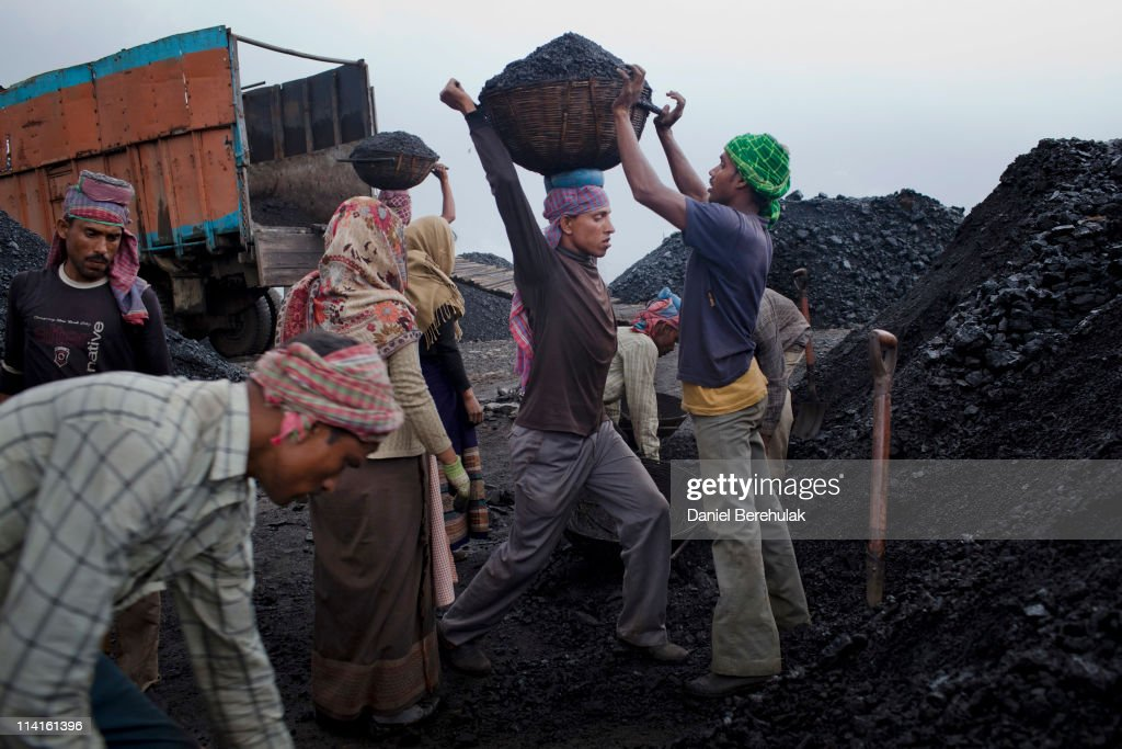 Workers load coal onto a truck as they work at a coal depot on April 14, 2011 near Lad Rymbai, in the district of Jaintia Hills, India. The Jaintia hills, located in India's far North East state of Meghalaya, miners descend to great depths on slippery, rickety wooden ladders. Children and adults squeeze into rat hole like tunnels in thousands of privately owned and unregulated mines, extracting coal with their hands or primitive tools and no safety equipment. Workers can earn as much as 150 USD per week or 30,000 Rupees per month, significantly higher than the national average of 15 USD per day. After traversing treacherous mountain roads, the coal is delivered to neighbouring Bangladesh and to Assam from where it is distributed all over India, to be used primarily for power generation and as a source of fuel in cement plants. Many workers leave homes in neighbouring states, and countries, like Bangladesh and Nepal, hoping to escape poverty and improve their quality of life. Some send money back to loved ones at home, whilst many others squander their earnings on alcohol, drugs and prostitution in the dusty, coal mining towns like Lad Rymbai. Some of the labor is forced, and an Indian NGO group, Impulse, estimates that 5,000 privately-owned coal mines in Jaintia Hills employed some 70,000 child miners. The government of Meghalaya refuted this figure, claiming that the mines had only 222 minor workers. Despite the ever present dangers and hardships, children, migrants and locals flock to the mines hoping to strike it rich in India's wild east.