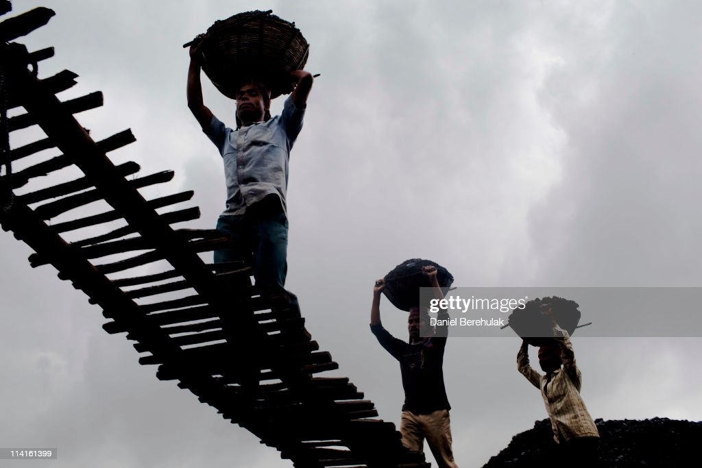 Workers load coal onto a truck at a coal depot on April 14, 2011 near Lad Rymbai, in the district of Jiantia Hills, India. The Jaintia hills, located in India's far North East state of Meghalaya, miners descend to great depths on slippery, rickety wooden ladders. Children and adults squeeze into rat hole like tunnels in thousands of privately owned and unregulated mines, extracting coal with their hands or primitive tools and no safety equipment. Workers can earn as much as 150 USD per week or 30,000 Rupees per month, significantly higher than the national average of 15 USD per day. After traversing treacherous mountain roads, the coal is delivered to neighbouring Bangladesh and to Assam from where it is distributed all over India, to be used primarily for power generation and as a source of fuel in cement plants. Many workers leave homes in neighbouring states, and countries, like Bangladesh and Nepal, hoping to escape poverty and improve their quality of life. Some send money back to loved ones at home, whilst many others squander their earnings on alcohol, drugs and prostitution in the dusty, coal mining towns like Lad Rymbai. Some of the labor is forced, and an Indian NGO group, Impulse, estimates that 5,000 privately-owned coal mines in Jaintia Hills employed some 70,000 child miners. The government of Meghalaya refuted this figure, claiming that the mines had only 222 minor workers. Despite the ever present dangers and hardships, children, migrants and locals flock to the mines hoping to strike it rich in India's wild east.