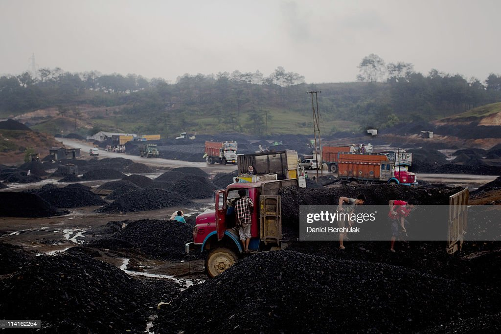 Workers load coal onto trucks at a coal depot on April 16, 2011 near to Lad Rymbai, in the district of Jaintia Hills, India. The Jaintia hills, located in India's far North East state of Meghalaya, miners descend to great depths on slippery, rickety wooden ladders. Children and adults squeeze into rat hole like tunnels in thousands of privately owned and unregulated mines, extracting coal with their hands or primitive tools and no safety equipment. Workers can earn as much as 150 USD per week or 30,000 Rupees per month, significantly higher than the national average of 15 USD per day. After traversing treacherous mountain roads, the coal is delivered to neighbouring Bangladesh and to Assam from where it is distributed all over India, to be used primarily for power generation and as a source of fuel in cement plants. Many workers leave homes in neighbouring states, and countries, like Bangladesh and Nepal, hoping to escape poverty and improve their quality of life. Some send money back to loved ones at home, whilst many others squander their earnings on alcohol, drugs and prostitution in the dusty, coal mining towns like Lad Rymbai. Some of the labor is forced, and an Indian NGO group, Impulse, estimates that 5,000 privately-owned coal mines in Jaintia Hills employed some 70,000 child miners. The government of Meghalaya refuted this figure, claiming that the mines had only 222 minor workers. Despite the ever present dangers and hardships, children, migrants and locals flock to the mines hoping to strike it rich in India's wild east.