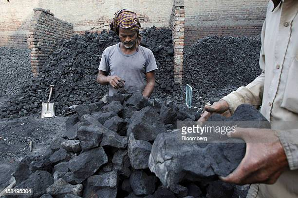 Workers load lumps of coal onto a bicycle trailer at a wholesaler in New Delhi India on Wednesday Nov 5 2014 Prime Minister Narendra Modi is seeking...