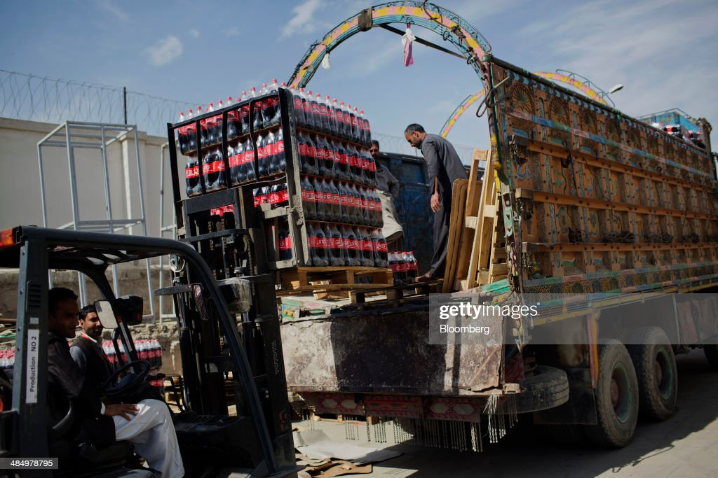 Workers load pallets of Coca-Cola Co. beverage at the Habib Gulzar Non-Alcoholic Beverage Ltd. bottling facility in Kabul, Afghanistan, on Thursday, April 10, 2014. Coca-Cola Co., the world's largest soda maker, today showed signs of a rebound in the first three months of the year, easing the concerns that arose when the company unsettled investors with surprisingly sluggish global sales in the fourth quarter. Photographer: Victor J. Blue/Bloomberg via Getty Images