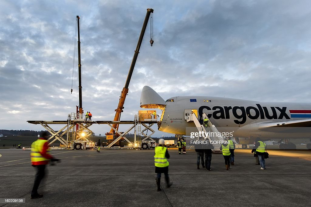 Workers load part of the Swiss sun-powered aircraft Solar Impulse into a Cargolux Boeing 747 cargo aircraft on February 20, 2013 at Payerne airport. The Boeing will carry Solar Impulse HB-SIA prototype aircraft to San Francisco for a serie of flights across America from the West to East Coast.