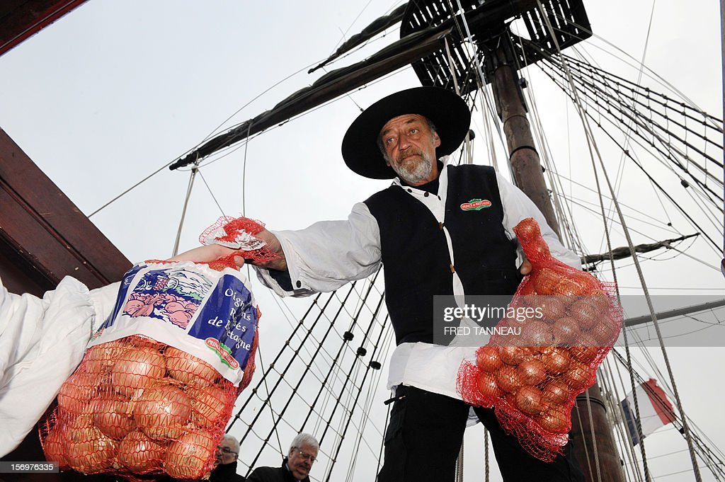 Workers load pink onions destined for Great Britain aboard the Etoile du Roy (Star of the King), a replica of an 18th-century sailing ship, on November 24, 2012 in Roscoff, western France. 'Onion Johnnies', the travelling salesmen whose berets and bicycles inspired Britain and much of the world's classic image of the archetypal Frenchman, are setting sail for England once more. The boat, weighed down by the hefty cargo, will assure the delivery of the onions to London on December 6, after stopovers on the Channel island of Jersey and at Portsmouth, on England's southern coast. The first French onion salesman to try his luck in England set sail from Roscoff in 1828.