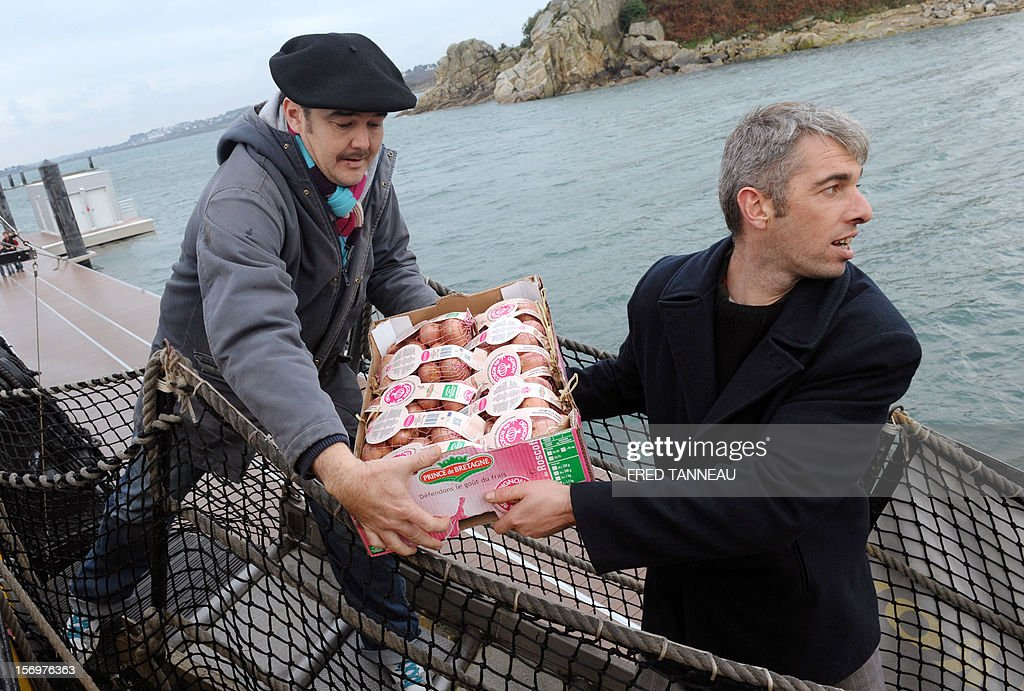Workers load pink onions destined for Great Britain aboard the Etoile du Roy (Star of the King), a replica of an 18th-century sailing ship, on November 24, 2012 in Roscoff, western France. 'Onion Johnnies', the travelling salesmen whose berets and bicycles inspired Britain and much of the world's classic image of the archetypal Frenchman, are setting sail for England once more. The boat, weighed down by the hefty cargo, will assure the delivery of the onions to London on December 6, after stopovers on the Channel island of Jersey and at Portsmouth, on England's southern coast. The first French onion salesman to try his luck in England set sail from Roscoff in 1828. AFP PHOTO / FRED TANNEAU