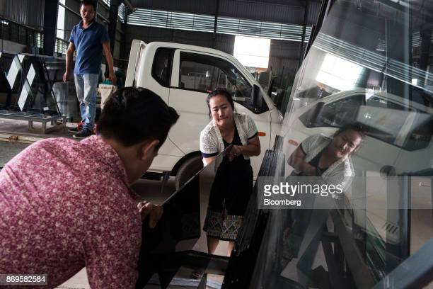 Workers load up a sheet of glass onto a truck at the Somvang Glass Factory on the outskirts of Vientiane Laos on Wednesday Nov 1 2017 Asia'ssmallest...