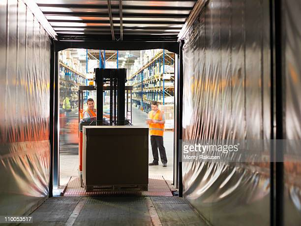 Workers loading truck with forklift