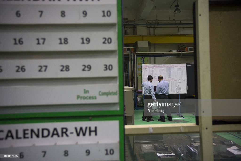 Workers look at a chart at the Motherson Sumi Systems Ltd. (MSSL) injection molding plant in Noida, India, on Thursday, Feb. 28, 2013. Motherson Sumi Systems Ltd., 25 percent owned by Sumitomo Electric Industries Ltd. and India's biggest auto parts maker, supplies rear view mirrors, bumpers and body panels to clients including Porsche Automobil Holding SE, Bayerische Motoren Werke AG and Volkswagen AG. Photographer: Brent Lewin/Bloomberg via Getty Images