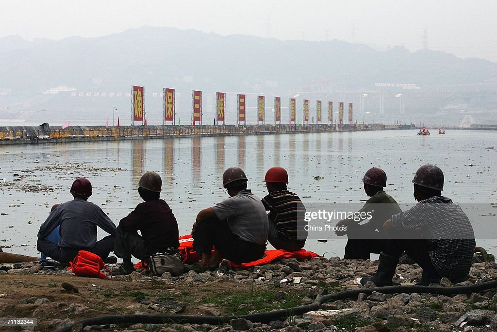 Workers look at the cofferdam protecting the justcompleted Three Gorges Dam as they sit on the shore on June 5 2006 in Yichang of Hubei Province...