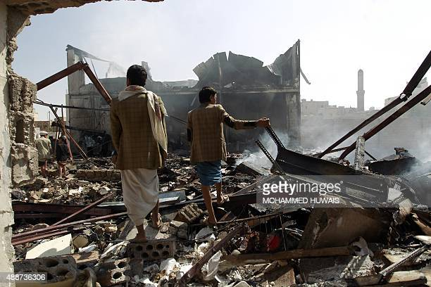Workers look at the destruction at a chocolate factory on September 17 2015 which was destroyed by air strikes carried out by the Saudiled coalition...