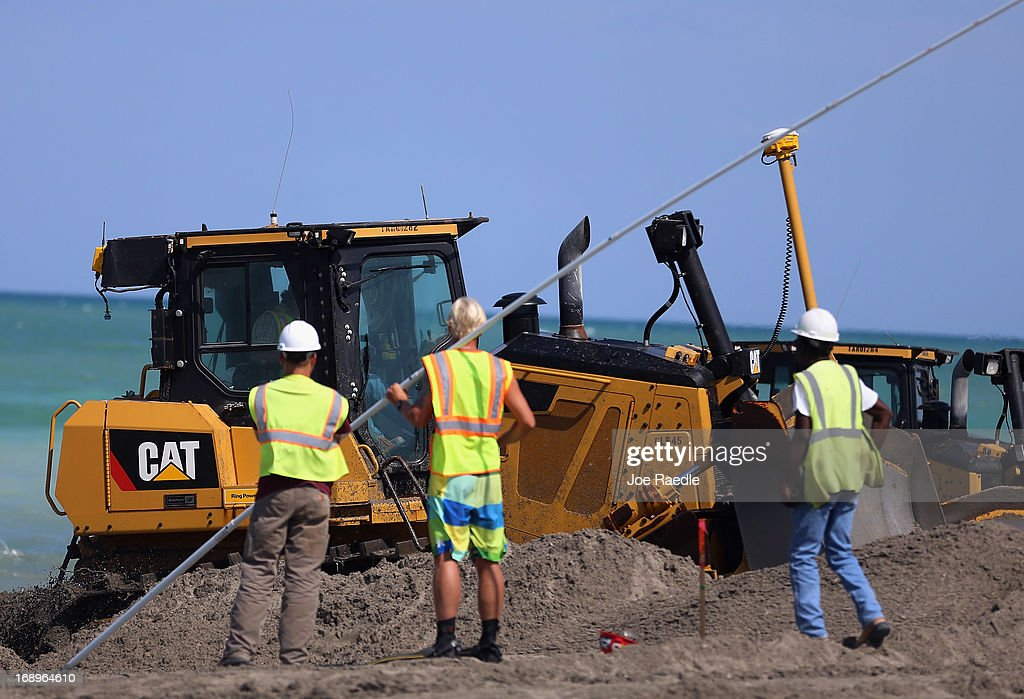 Workers look on as a bulldozer is used is used to push sand from a discharge pipe into place during a federally funded shore protection project by Great Lakes Dredge and Dock on May 17, 2013 in Fort Pierce, Florida. As cities along the East Coast prepare for the start of the hurricane season, officials say the area encompasing Fort Pierce beach has been in dire need of repair since Hurricane Sandy last year made worse an area already suffering significantly from erosion. Some experts say shore restoration projects can help reduce the physical and economic damage from waves, storm surge, and the resulting coastal flooding in a hurricane.