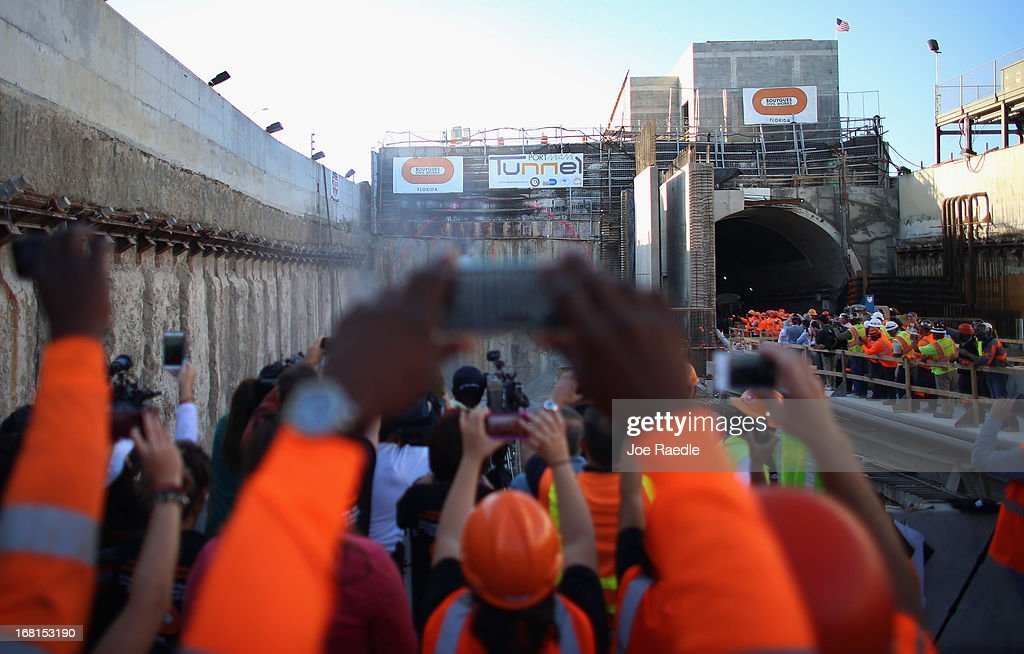 Workers look on as the massive drill nicknamed Harriet breaks through the last bit of soil on Watson Island on May 6, 2013 in Miami, Florida. The emergence of the drill completed the second leg of the 13 month-old, billion dollar Miami Tunnel project, which when finished will connect the mainland to the Port of Miami.