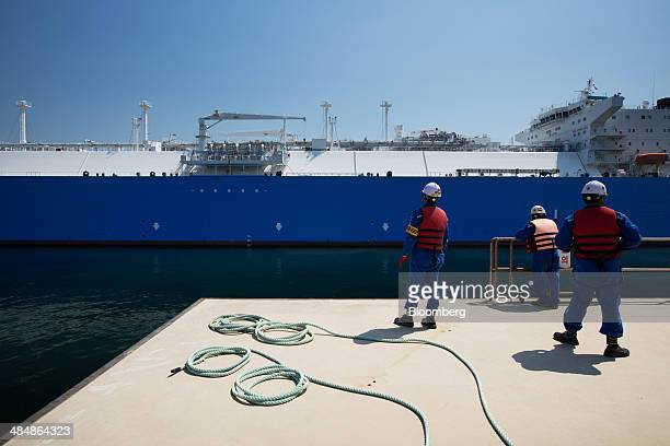 Workers look out from the dock as the Tangguh Palung liquefied natural gas tanker operated by Tangguh LNG approaches the Korea Gas Corp LNG terminal...