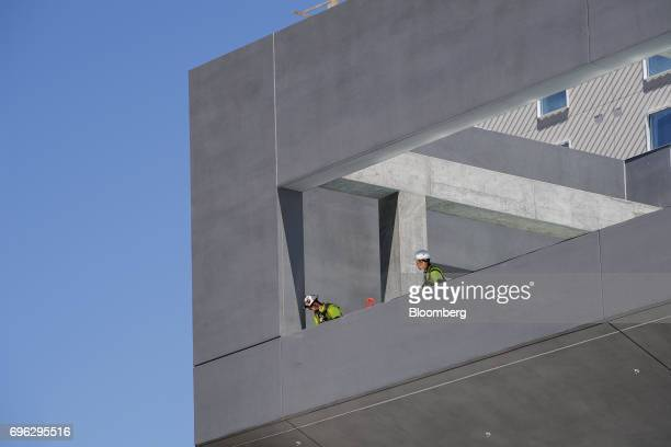 Workers look over the edge of a building under construction in Sacramento California US on Tuesday June 6 2017 As the cost of daily life tests the...