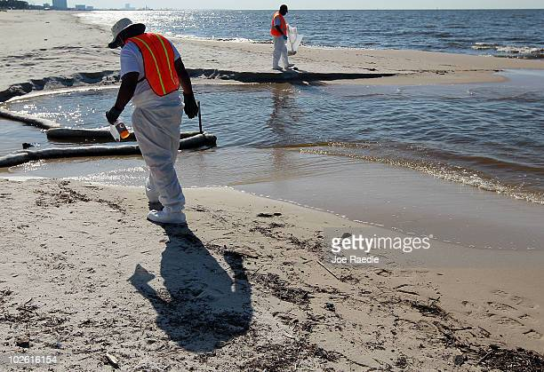 Workers look to clear off some of the oil residue on the beach from the Deepwater Horizon oil spill in the Gulf of Mexico on July 4 2010 in Biloxi...