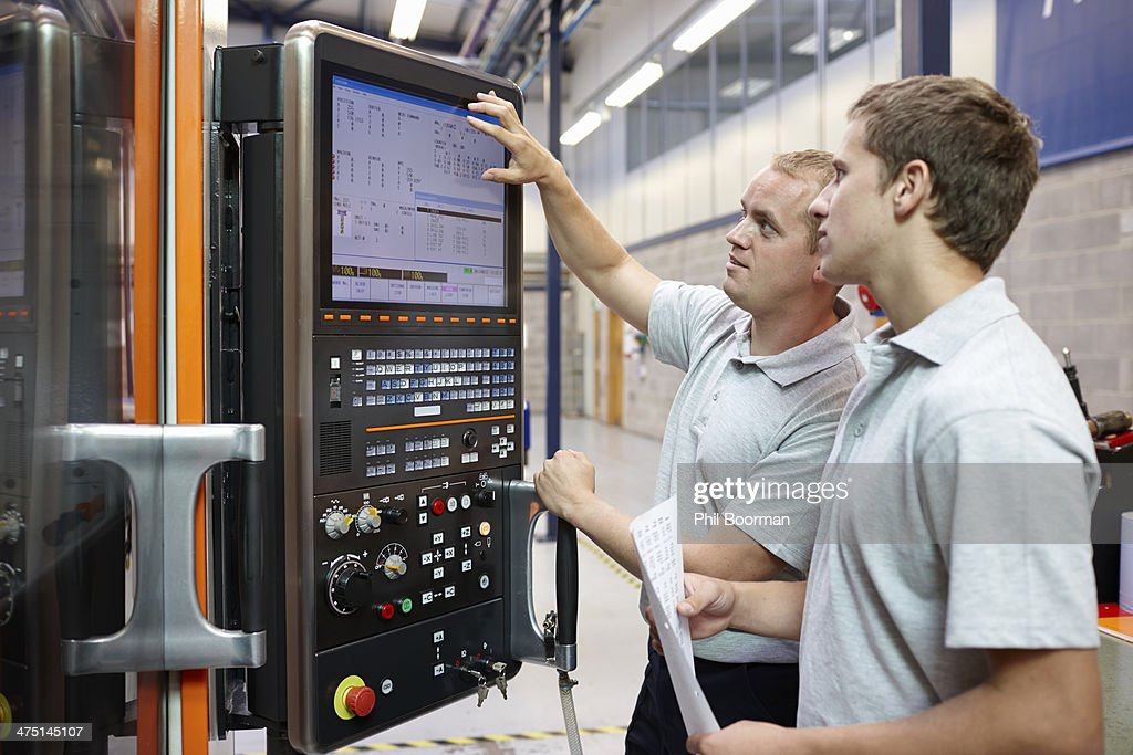 Workers looking at computer monitor in engineering factory