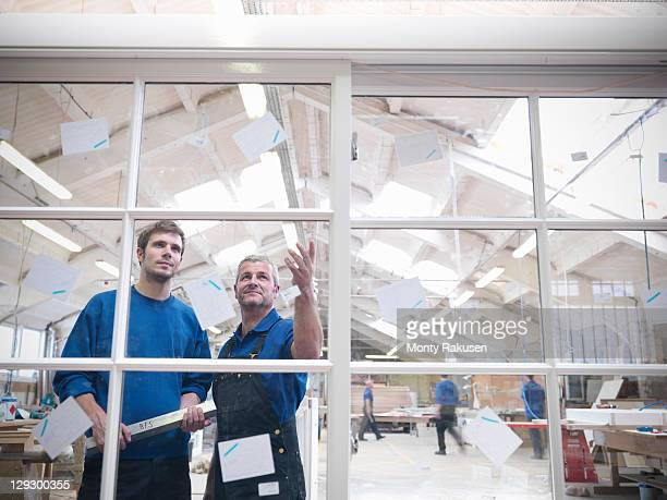 Workers looking at window frames in joinery