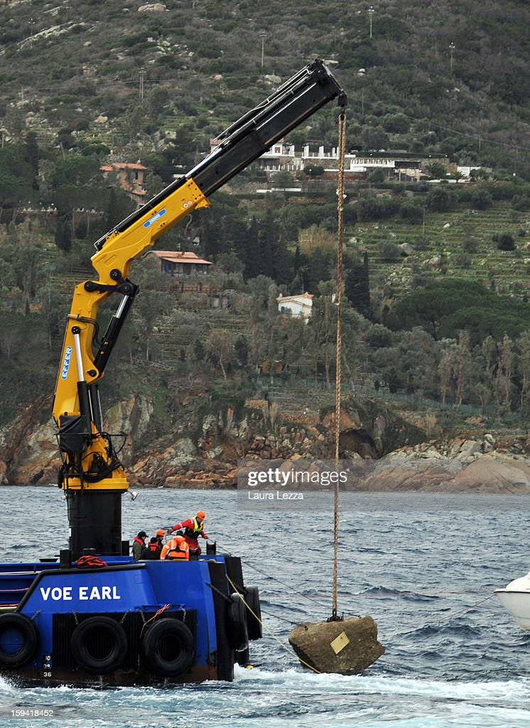 Workers lower a piece of the massive rock that was embedded in the hull of the Costa Concordia back into the sea on January 13, 2013 in Giglio Porto, Italy. A year after the sinking of the ship Costa Concordia, relatives of the victims, survivors, island residents, law enforcement and institutions gathered to mark the first anniversary and commemorate the dead. More than four thousand people were on board when the ship hit a rock off the Tuscan coast, killing 32 and leaving two people missing.
