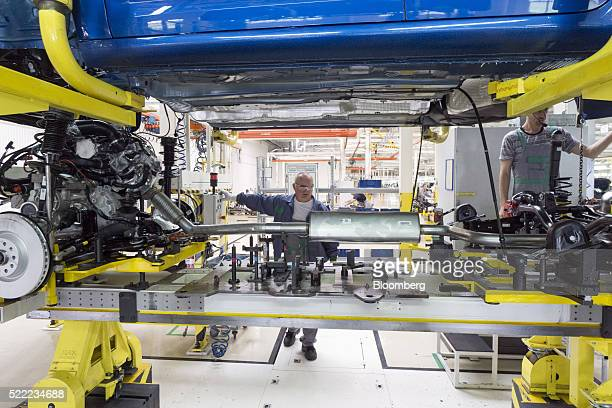 Workers lower the body onto the chassis and exhaust pipe of a Skoda Superb automobile at the Eurocar PJSC automotive plant in Solomonovo Ukraine on...