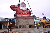 Workers lower the landmark 22 foot high Santa Claus statue onto a trailer after removing it from the roof of a candy store on Santa Claus Lane in...