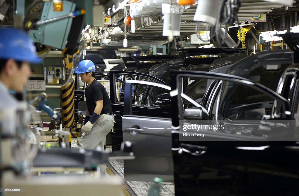 Workers make a final inspection on Mitsubishi Motors Corp. vehicles on the production line of the Mitsubishi Motors Mizushima plant in Kurashiki, Okayama Prefecture, Japan, on Monday, May 20, 2013. Nissan will start selling the first minicar it jointly developed with Mitsubishi Motors in Japan next month amid increasing demand from the nation's consumers for smaller and cheaper vehicles. Photographer: Tomohiro Ohsumi/Bloomberg via Getty Images