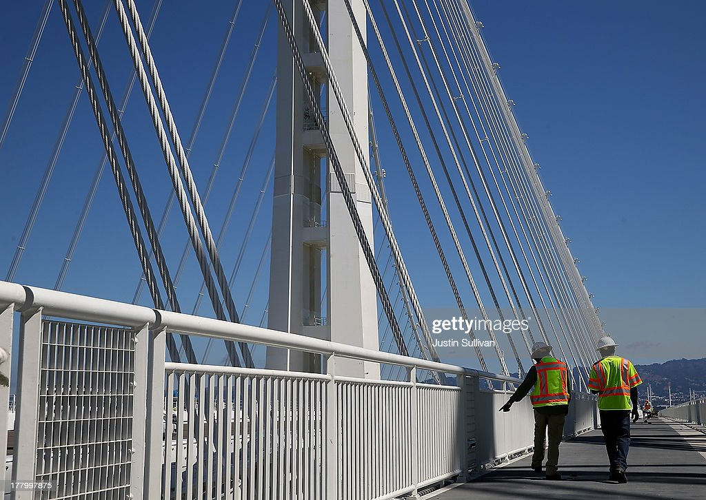 Workers make adjustements to a bike path next to the new Bay Bridge Self-Anchored Suspension (SAS) tower on August 26, 2013 in San Francisco, California. After nearly 12 years of construction and an estimated price tag of $6.4 billion, the new eastern span of the Bay Bridge is set to open on September 3. The bridge will be the world's tallest Self-Anchored Suspension (SAS) tower once completed.