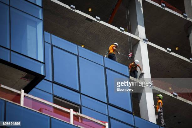Workers make adjustments during construction on the 416 Kent Avenue apartment development in the Williamsburg neighborhood of the Brooklyn borough of...