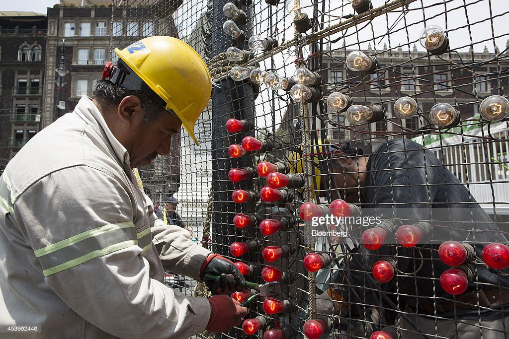 Workers make adjustments to the light bulbs on an illuminated sign in the traditional main plaza known as the Zocalo in Mexico City, Mexico, on Thursday, Aug. 21, 2014. Mexican consumer prices rose more than analysts expected in the first half of August and the unemployment rate rose to 5.47 percent in July compared with 4.8 percent in June. Photographer: Susana Gonzalez/Bloomberg via Getty Images