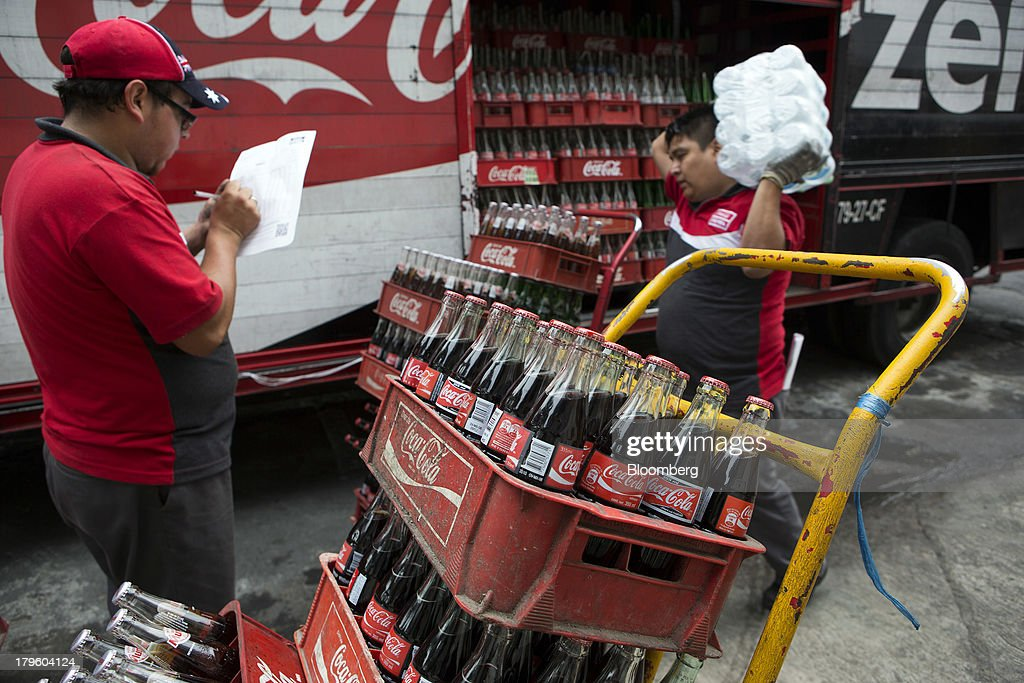 Workers make deliveries of Coca-Cola products in Mexico City, Mexico, on Thursday, Sept. 5, 2013. Coca-Cola Femsa SAB, a bottler and distributor of Coca-Cola products in Mexico, agreed to buy Brazils Spaipa SA Industria Brasileira de Bebidas in a cash deal with a total transaction value of $1.86 billion. Photographer: Susana Gonzalez/Bloomberg via Getty Images