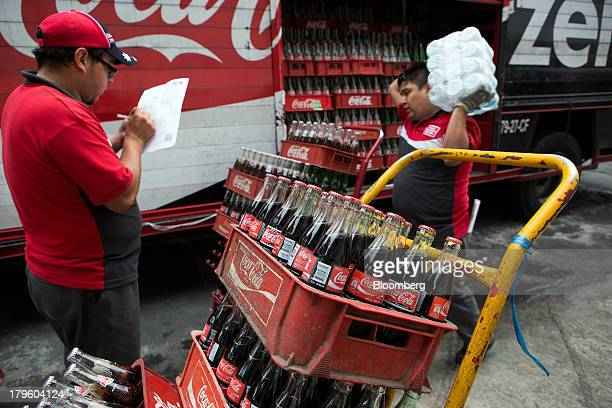 Workers make deliveries of CocaCola products in Mexico City Mexico on Thursday Sept 5 2013 CocaCola Femsa SAB a bottler and distributor of CocaCola...