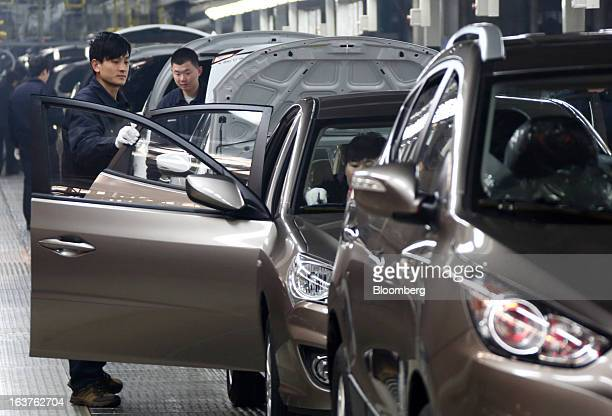 Workers make final inspections on Beijing Hyundai Motor Co cars on the production line at the company's plant in Beijing China on Friday March 15...