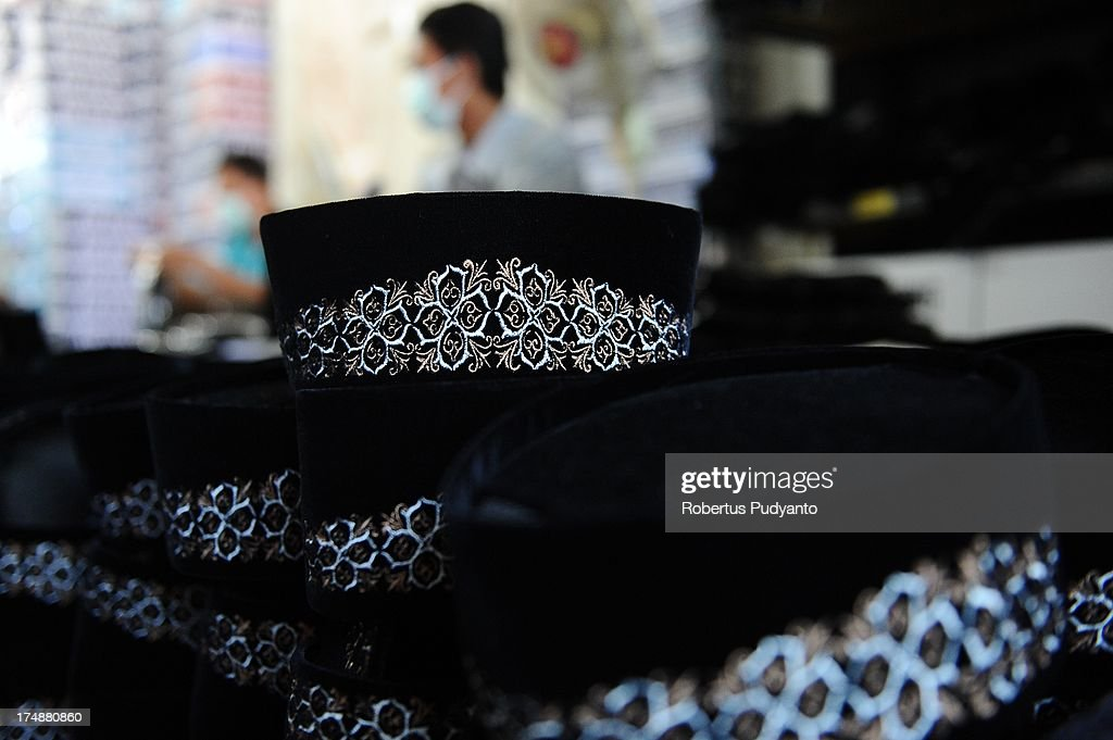 Workers make finishing touches to skull caps before they are put in a box at Awing traditional Muslim skull cap manufacturers on July 29, 2013 in Gresik, Java, Indonesia. Awing traditional Muslim skull cap manufacturers have received increased demand for their products from Singapore, Malaysia, Brunei Darussalam, as well as domestic buyers, with sales increasing from from 30,000 to 50,000 pieces during the Ramadan period. This skull cap does not crease and has the advantages of good ventilation. The paperless skull cap body is made from high quality velvet material imported from Korea and the United States, with lining materials imported from Japan.