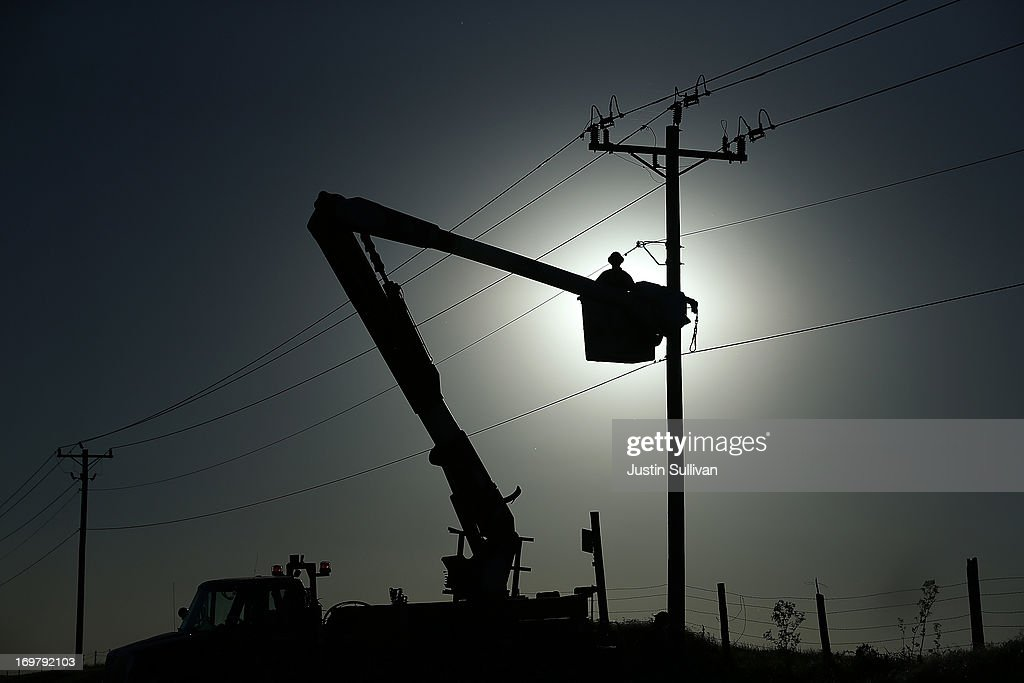 Workers make reapairs to power lines following a series of tornadoes that ripped through the area a day earlier on June 1, 2013 in El Reno, Oklahoma. A series of tornadoes ripped through the area on Friday evening killing at least nine people, injuring many others and destroying homes and buildings.