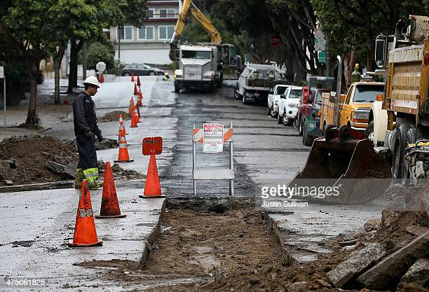 Workers make repairs to a street on February 26 2014 in San Francisco California During a visit to St Paul Minnesota US President Barack Obama...