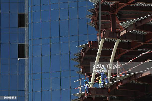 Workers maneuver a part into place on a construction site in the budding new financial district on October 23 2011 in Doha Qatar Qatar will host the...
