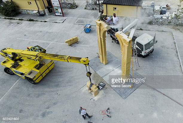 Workers manoeuvre the final block into place to complete the 3D marble replica of Palmyra's Arch of Triumph at the marble caves of Carrara on April...