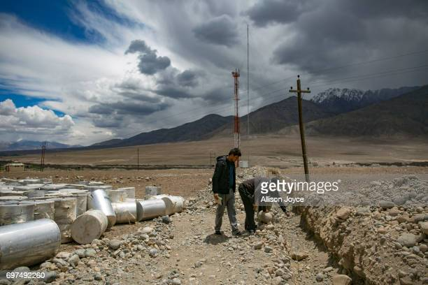 Workers measure a solar water pipeline at the site of what will be a solar energy park built by the Ladakh Renewable Energy Development Agency in Leh...