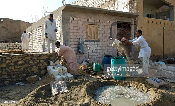 Workers mix cement for a new house of stone and white brick under construction in Siwa Egypt on Thursday Jan 17 2008 Located in the Libyan Desert...