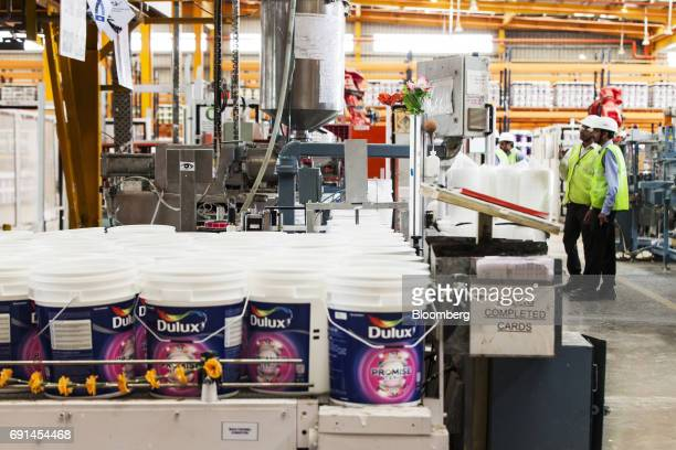 Workers monitor Dulux branded paint buckets as they move along a filling line at an Akzo Nobel India Ltd factory in Gwalior Madhya Pradesh India on...