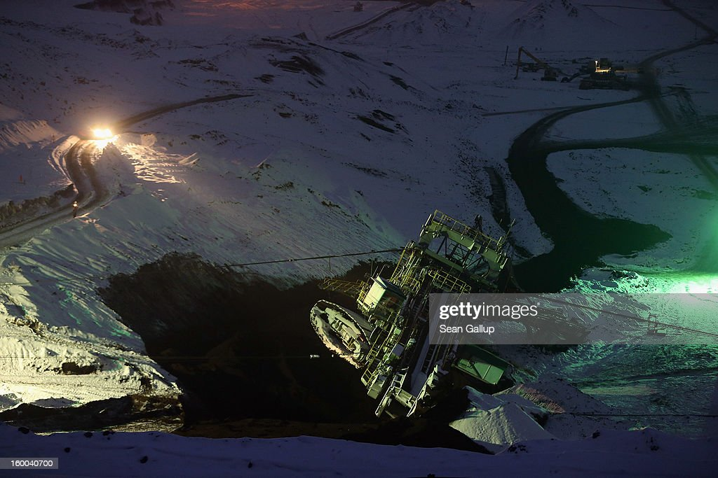 Workers monitor progress as they attempt to set a 950-tonne bucket excavator upright over the course of several hours following an accident at an open-pit coal mine on January 25, 2013 near Deutzen, Germany. The bucket excavator tipped over last summer after plateaus of earth and sand nearby gave way, pushing a layer of coal underneath. The excavator had been lying severaly tilted to one side ever since at the Vereinigtes Schleenhain mine, which is operated by Mibrag. Open-pit lignite coal mines are still common across eastern Germany and produce coal for local electricity production.