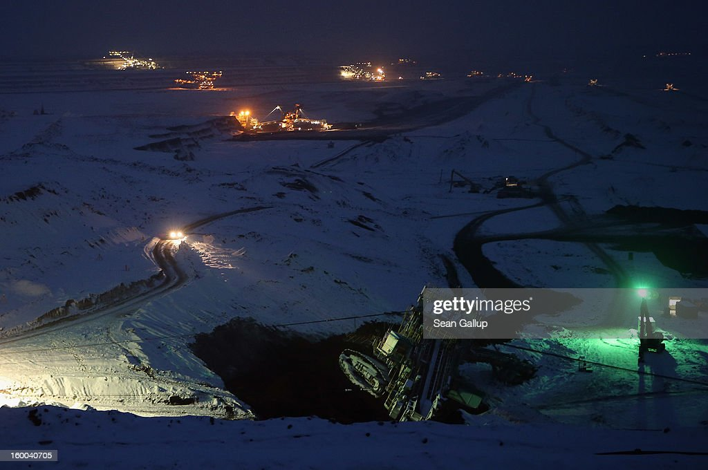 Workers monitor progress as they attempt to set a 950-tonne bucket excavator upright over the course of several hours following an accident at an open-pit coal mine as other excavators stand illuminated behind on January 25, 2013 near Deutzen, Germany. The bucket excavator tipped over last summer after plateaus of earth and sand nearby gave way, pushing a layer of coal underneath. The excavator had been lying severaly tilted to one side ever since at the Vereinigtes Schleenhain mine, which is operated by Mibrag. Open-pit lignite coal mines are still common across eastern Germany and produce coal for local electricity production.