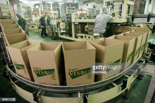 Workers monitor the packaging of bottles of palm cooking oil into cardboard boxes at Yee Lee Corp's Yee Lee Edible Oils factory in Ipoh Perak...
