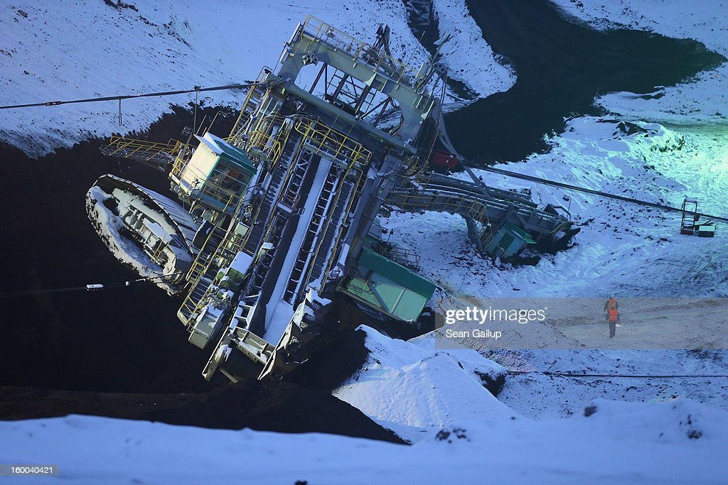Workers montior progress as they attempt to set a 950-tonne bucket excavator upright over the course of several hours following an accident at an open-pit coal mine on January 25, 2013 near Deutzen, Germany. The bucket excavator tipped over last summer after plateaus of earth and sand nearby gave way, pushing a layer of coal underneath. The excavator had been lying severaly tilted to one side ever since at the Vereinigtes Schleenhain mine, which is operated by Mibrag. Open-pit lignite coal mines are still common across eastern Germany and produce coal for local electricity production.