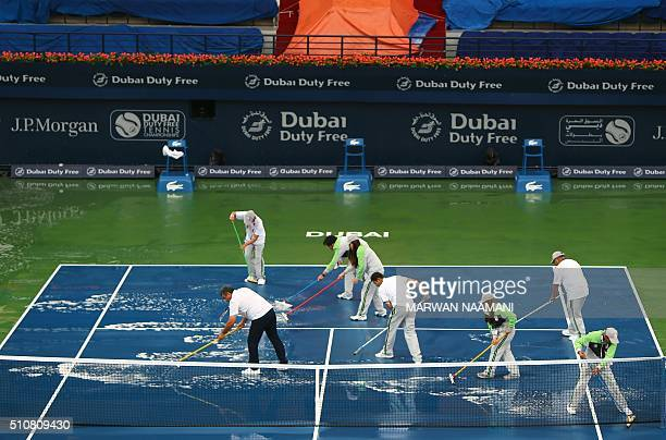 Workers mop water from the tennis stadium following heavy rain and hail that interrupted the WTA tennis match between French tennis player Caroline...