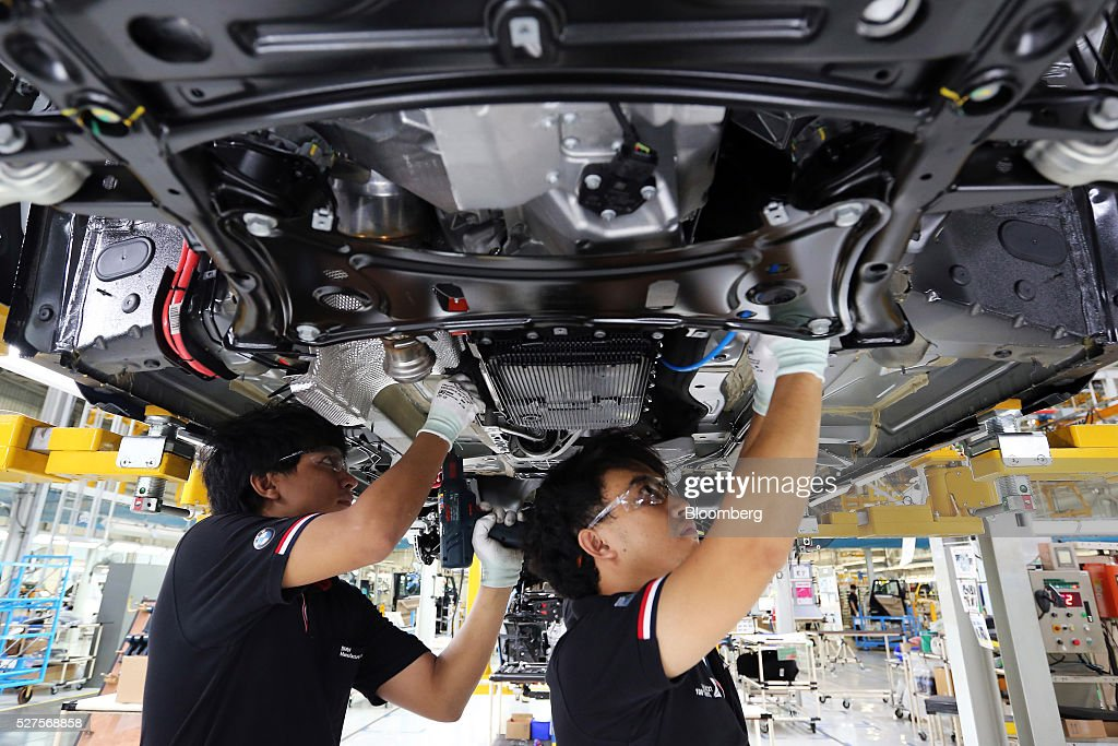 BMW AG workers mount an engine and transmission on a X3 vehicle at a BMW manufacturing plant in Pluak Daeng, Rayong Province, Thailand, on Tuesday, May 3, 2016. BMW's profit declined 2.5 percent in the first quarter on investment in new technologies like self-driving cars to defend its status as the world's biggest maker of luxury vehicles. Photographer: Dario Pignatelli/Bloomberg via Getty Images