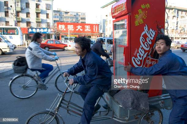 Workers move a Coke refrigerator on a tricycle March 4 2004 in Beijing According to ACNielsen CocaCola has a fifty percent share of China's beverage...
