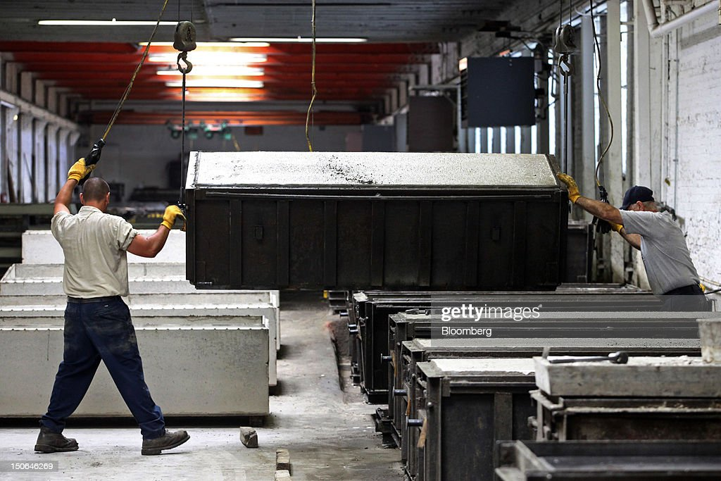 Workers move a concrete burial vault and its form at the American Wilbert Vault Corp. manufacturing facility in Des Plaines, Illinois, U.S., on Thursday, Aug. 23, 2012. Several U.S. Presidents including John F. Kennedy and Ronald Reagan, and other famous people including Al Capone, Louis Armstrong, Elvis Presley and Frank Sinatra are buried in American Wilbert burial vaults, according to the company. The U.S. Census Bureau is expected to release data on orders for durable goods on Aug. 24. Photographer: Tim Boyle/Bloomberg via Getty Images