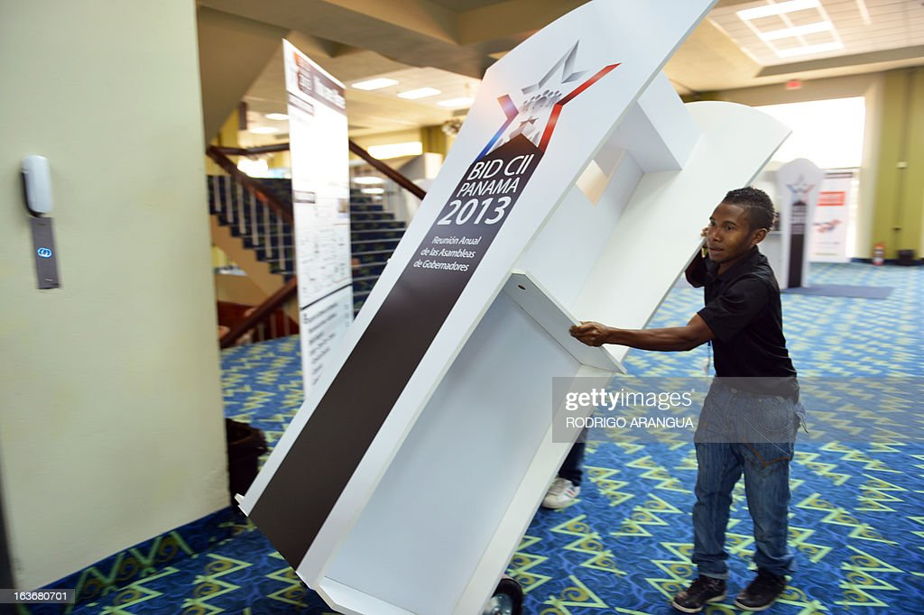 Workers move a cubicle before the start of the Annual Governors Meetings of the Inter-American Development Bank (IDB) in Panama City, on March 14, 2013. The Annual Meeting will take place in Panama City from March 14 to 17, 2013. AFP PHOTO/ Rodrigo ARANGUA