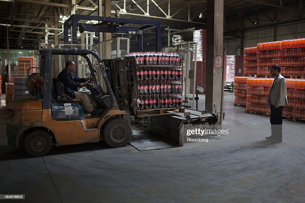 Workers move a pallet of Coca-Cola Co. beverage at the Habib Gulzar Non-Alcoholic Beverage Ltd. bottling facility in Kabul, Afghanistan, on Thursday, April 10, 2014. Coca-Cola Co., the world's largest soda maker, today showed signs of a rebound in the first three months of the year, easing the concerns that arose when the company unsettled investors with surprisingly sluggish global sales in the fourth quarter. Photographer: Victor J. Blue/Bloomberg via Getty Images